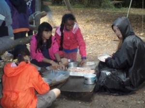Louveteaux et Jeannettes préparent le repas (dans une atmosphère un peu humide...)
